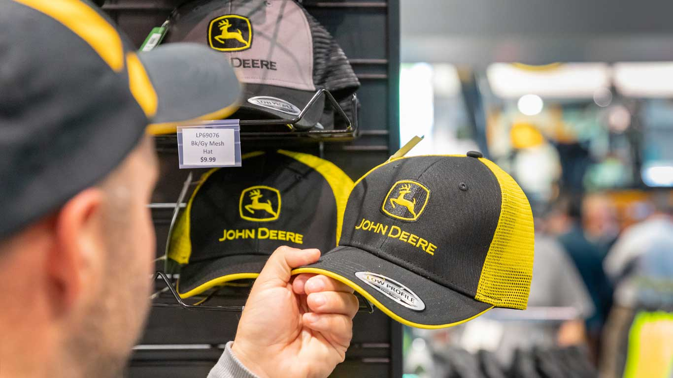An attendee browses the John Deere baseball cap selection in the merchandise store