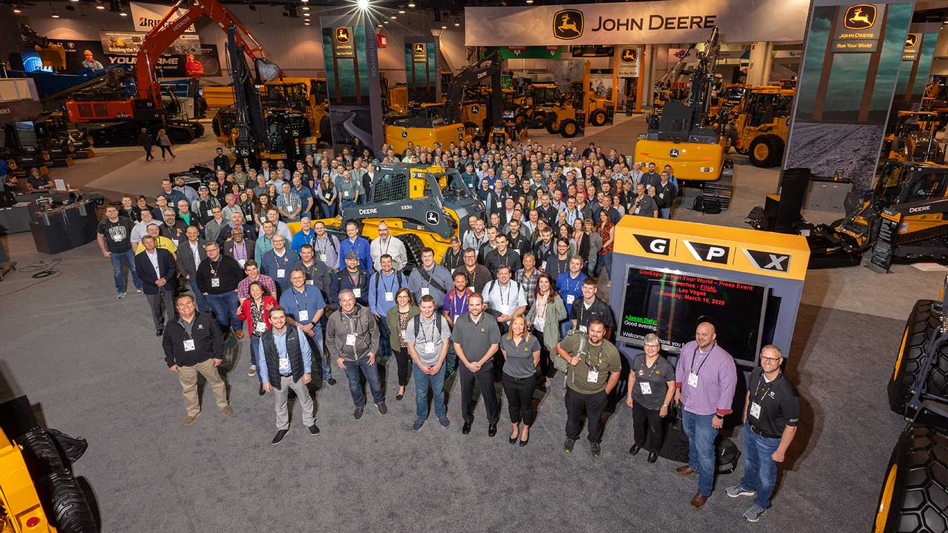 Hundreds of John Deere show workers pose for a photo in the middle of the Deere booth