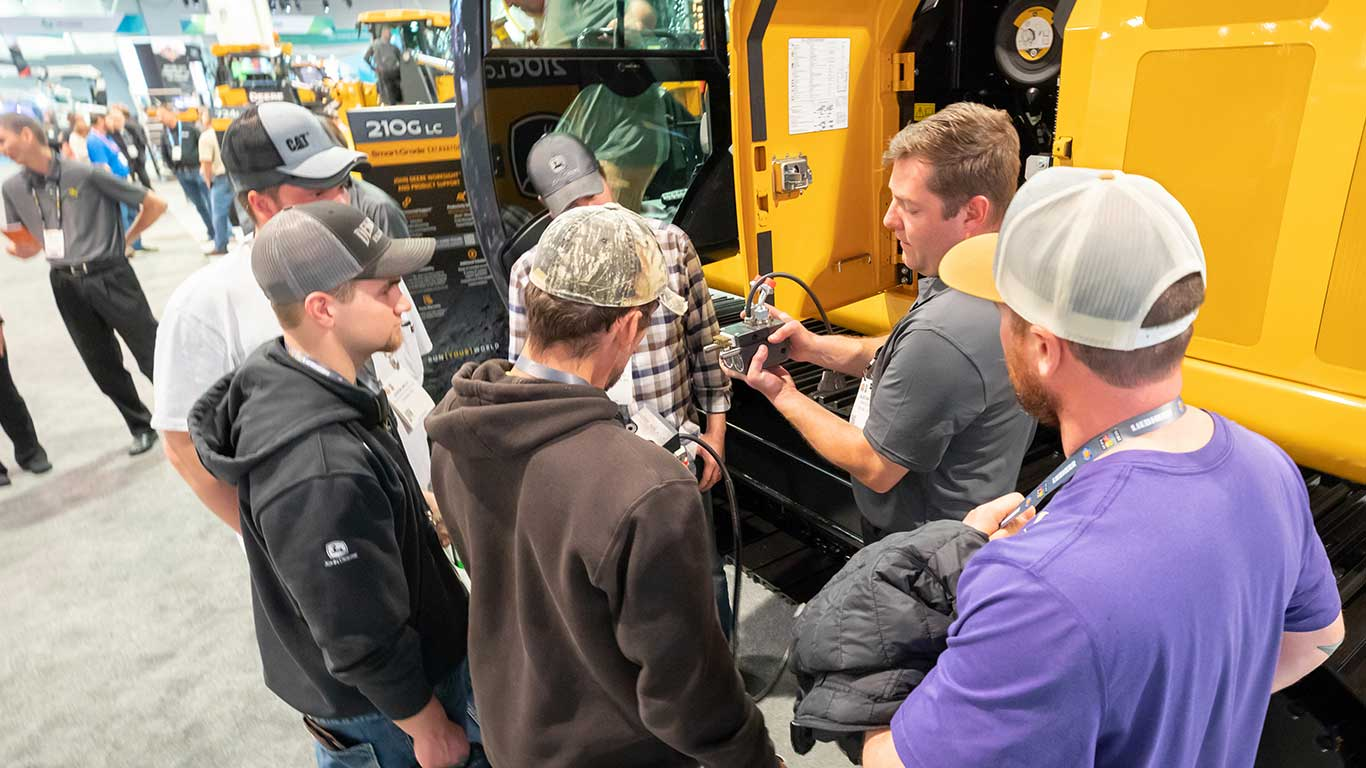 Four attendees gather around a machine as a Deere employee gives them information.