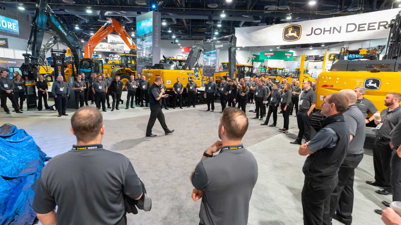 The Deere events manager stands in the middle of the show workers in the booth delivering a motivational speech