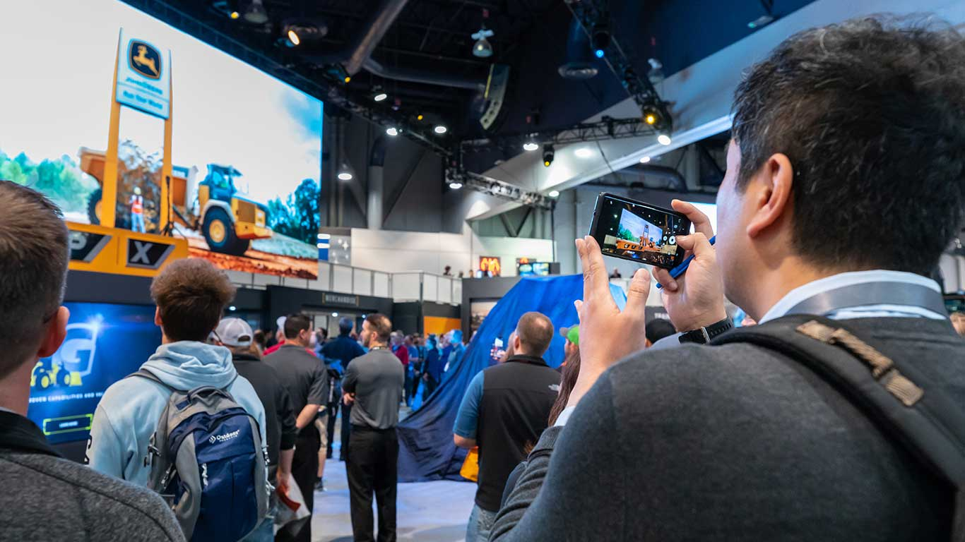 A view over the shoulder of an attendee who is filming the overhead video screen with his phone.