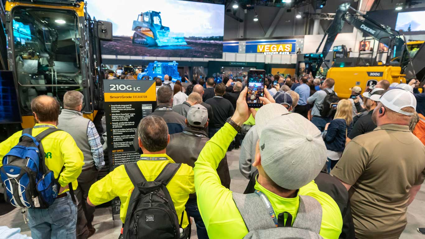 A large group of visitors mill around the John Deere booth