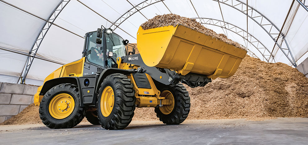 High-lift compact wheel loader moving manure