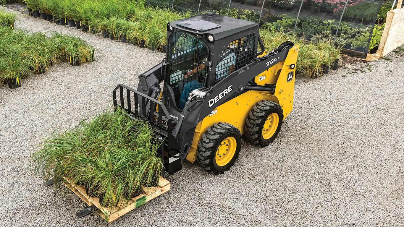 Skid steer moving a pallet of plants