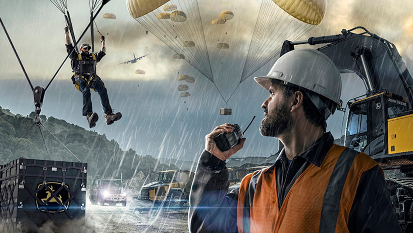 Deere dealer support personnel parachuting onto a fictional jobsite with shipping crates of parts