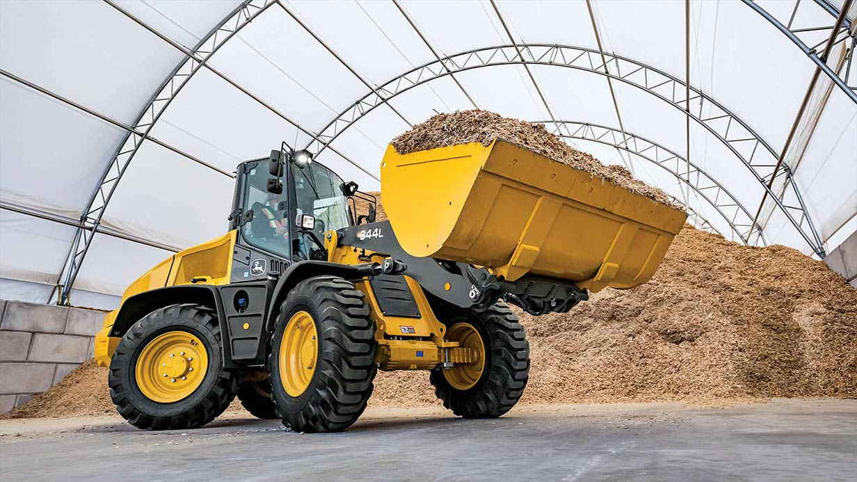 A John Deere 344L Compact Wheel Loader shown with a fully loaded bucket