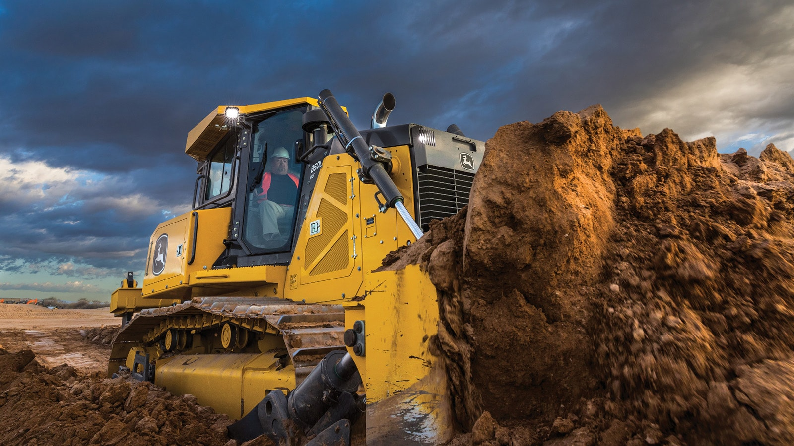 850L Dozer pushes a pile of dirt in front of a dramatic clouded sky