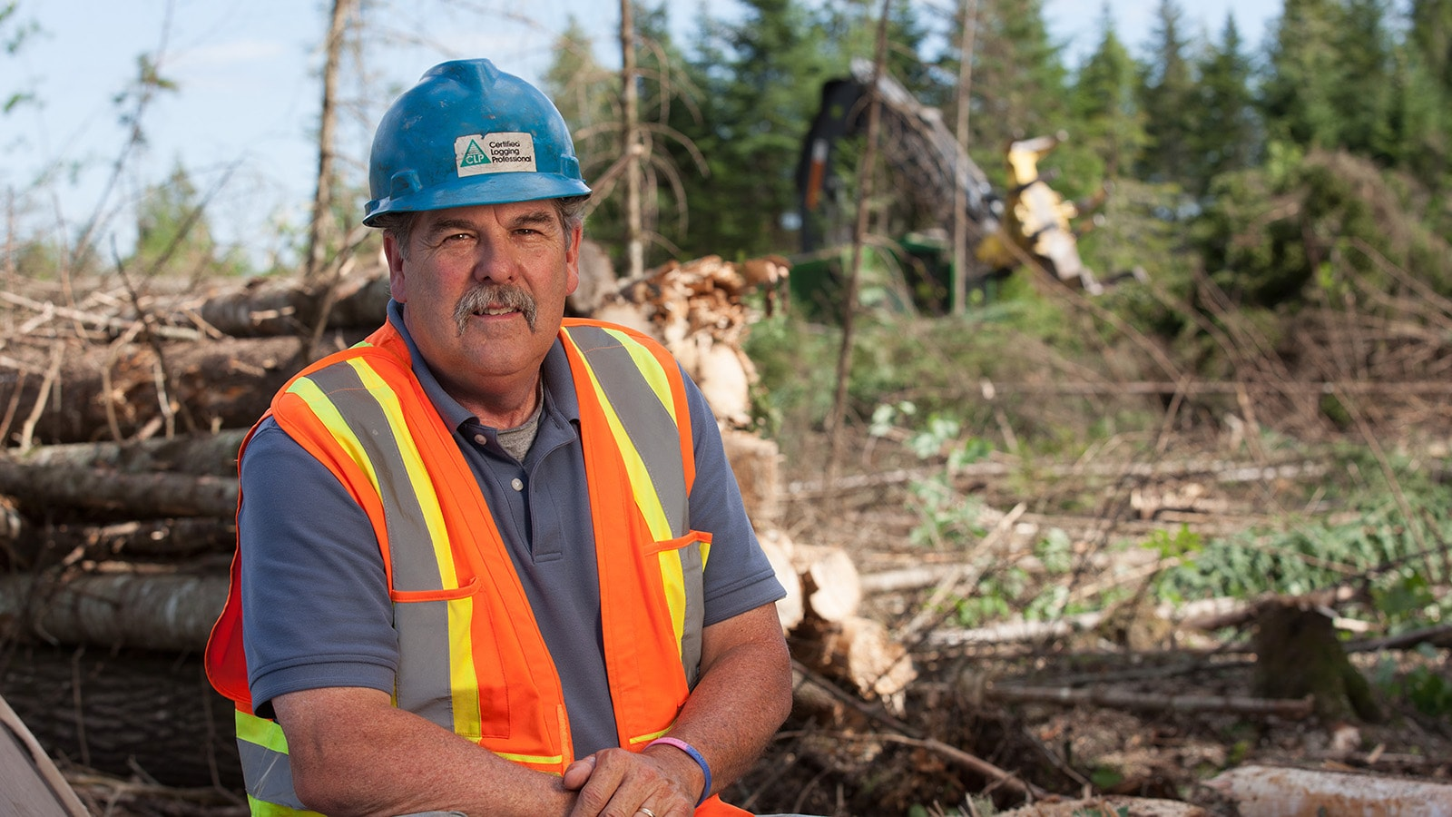 Dan Melcher poses with his logging operation in the background