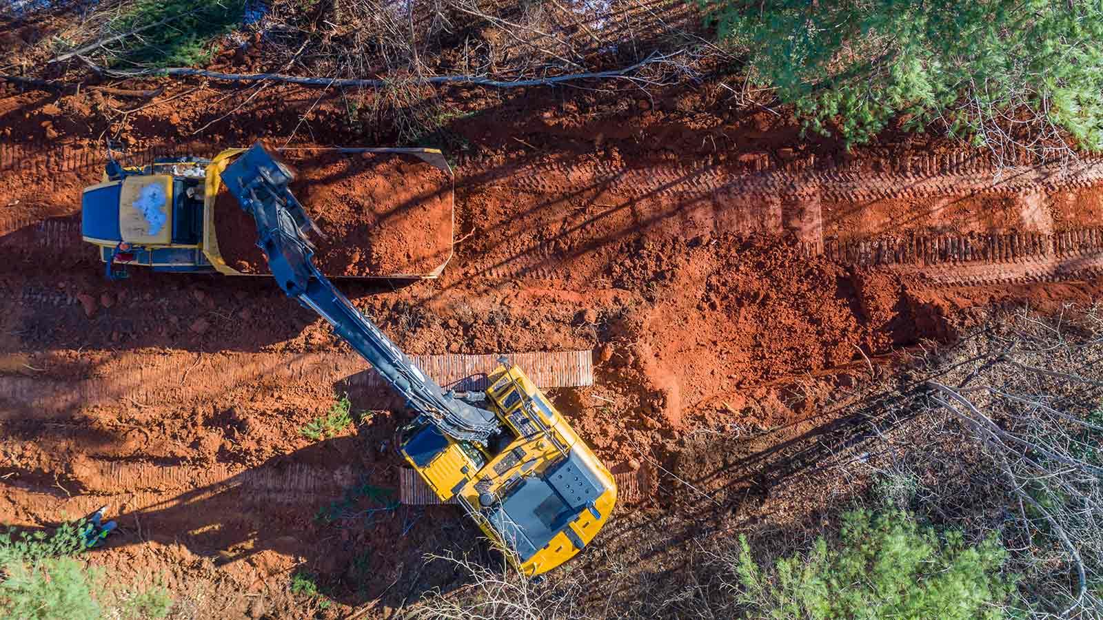 A John Deere 250G Excavator unloads a bucket of dirt into a John Deere 300D Articulated Dump Truck