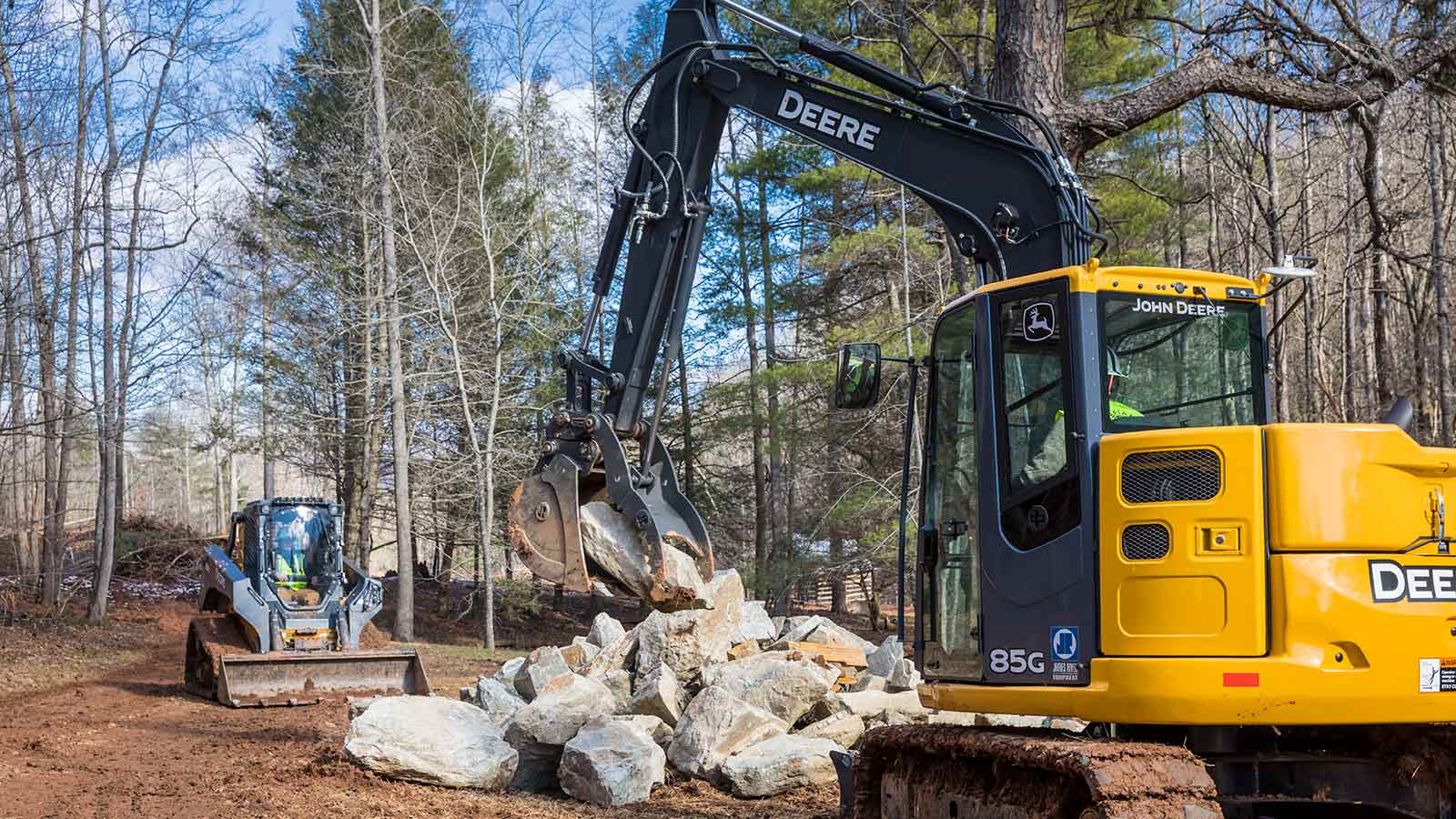 A John Deere 85G Mid-Size Excavator moves rocks with the assistance of a John Deere 333G Compact Track Loader
