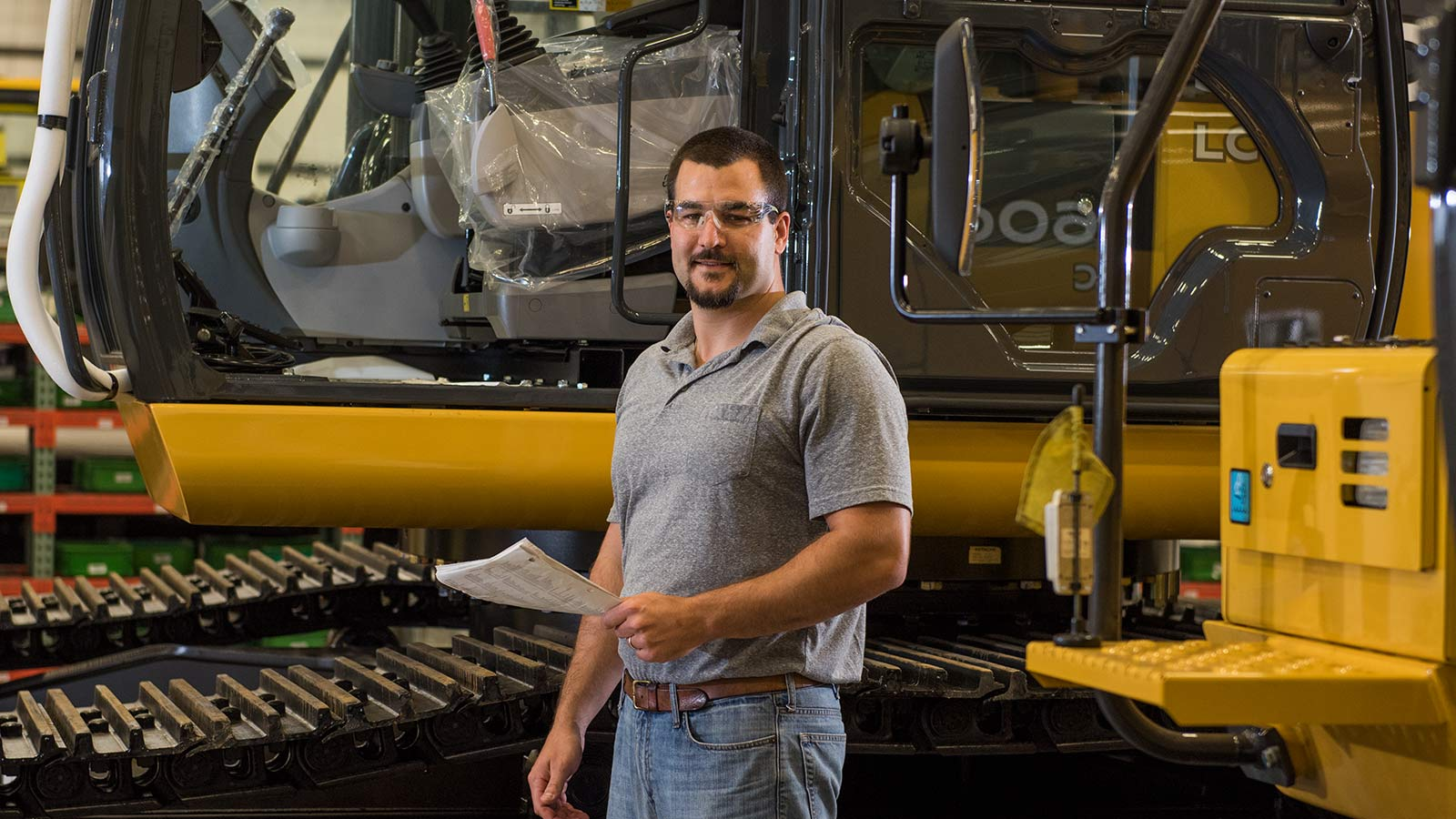 Jacob Henderson, a Product Development Process Design Engineer, shown working in the Deere-Hitachi factory in front of a John Deere excavator