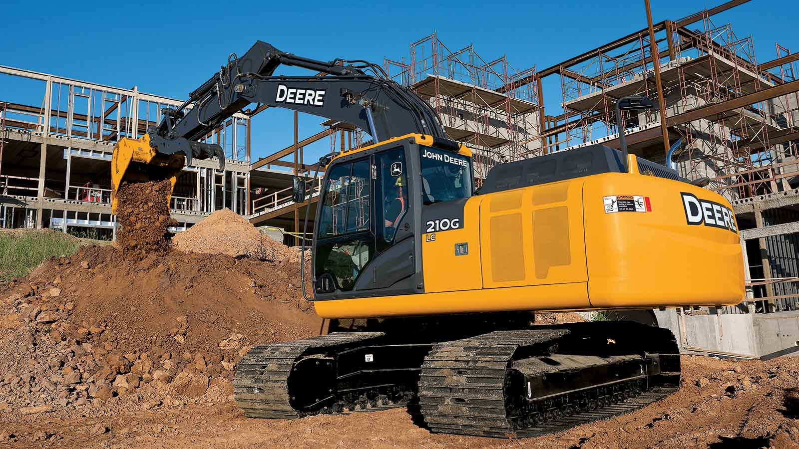 A John Deere 201G LC Excavator moves dirt on a commercial worksite.