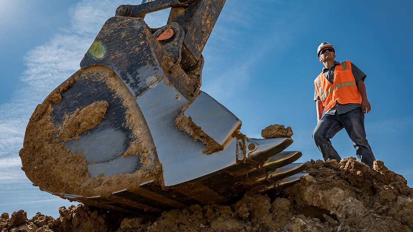 Tyler Cagle overlooks the job site next to the bucket of a John Deere 670G LC Excavator