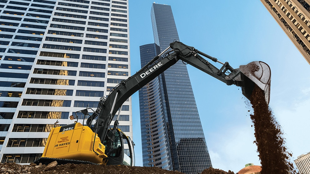 excavator working against city skyline