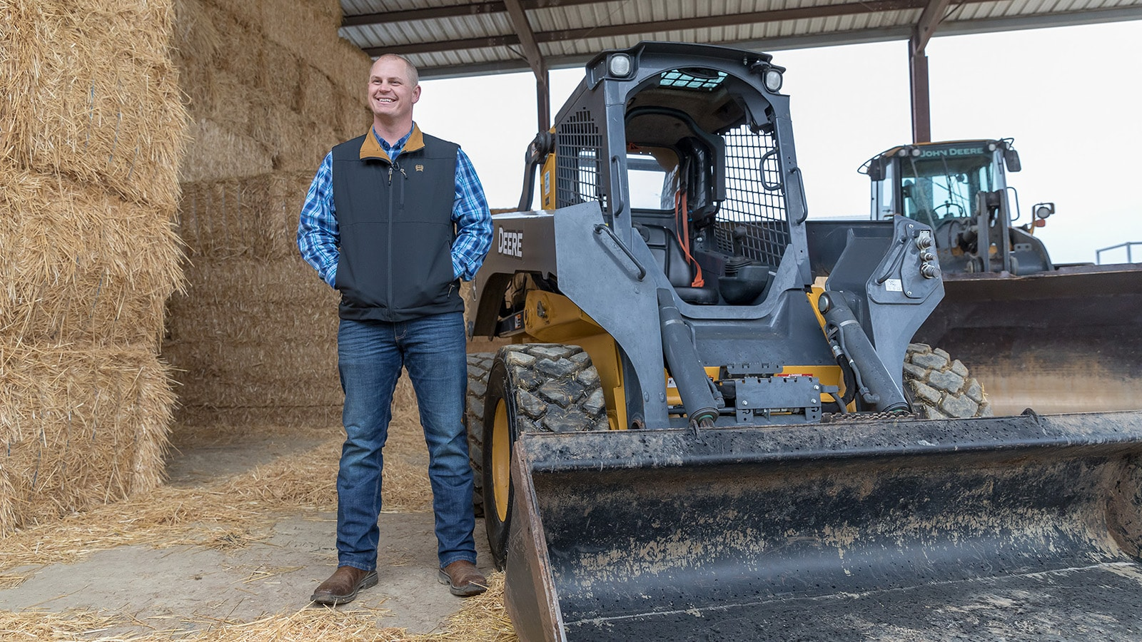 John Verwey stands next to his 332G Skid Steer with bales of hay in the background