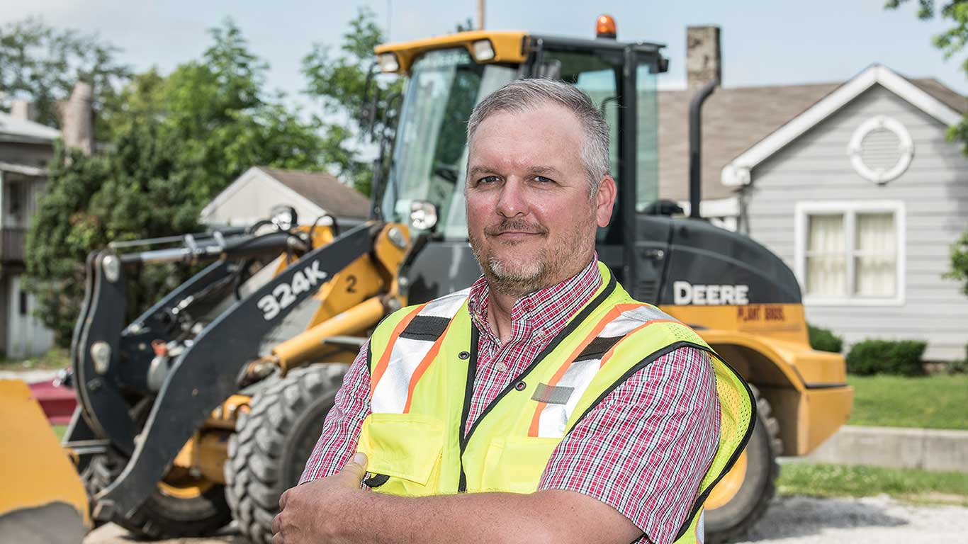 Jessie Plant from Plant Brothers Excavating poses with crossed arms in front of a 324K Wheel Loader on a residential street