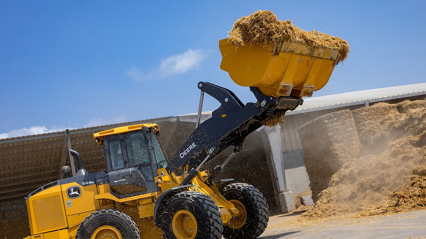 544L wheel loader moving loose bales of straw