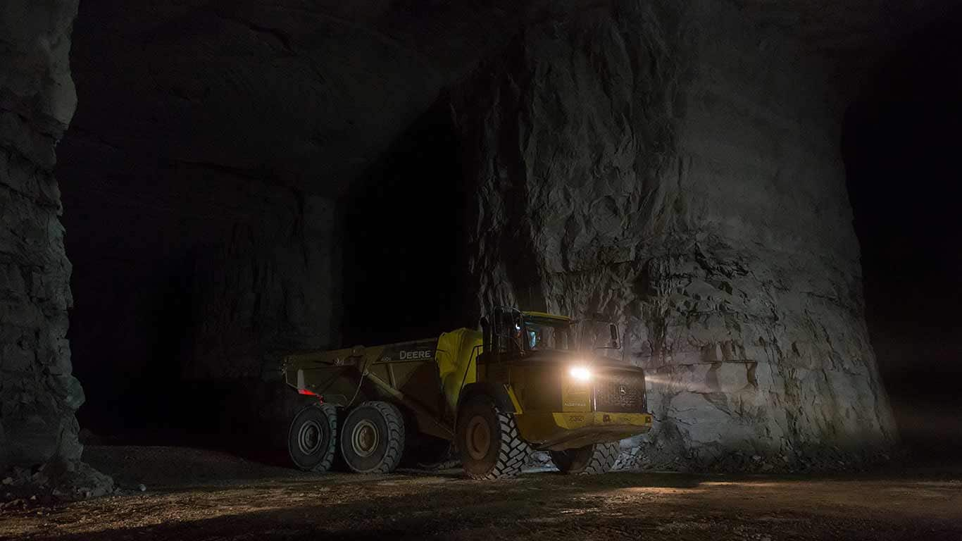 A dump truck drives through the underground mine