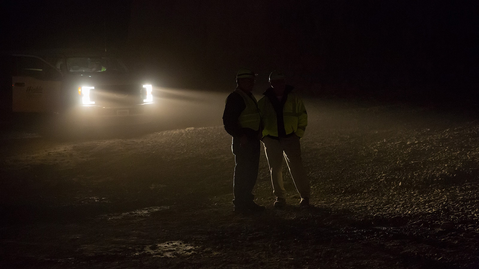 Two workers talk in the headlights of a pickup truck in the mine