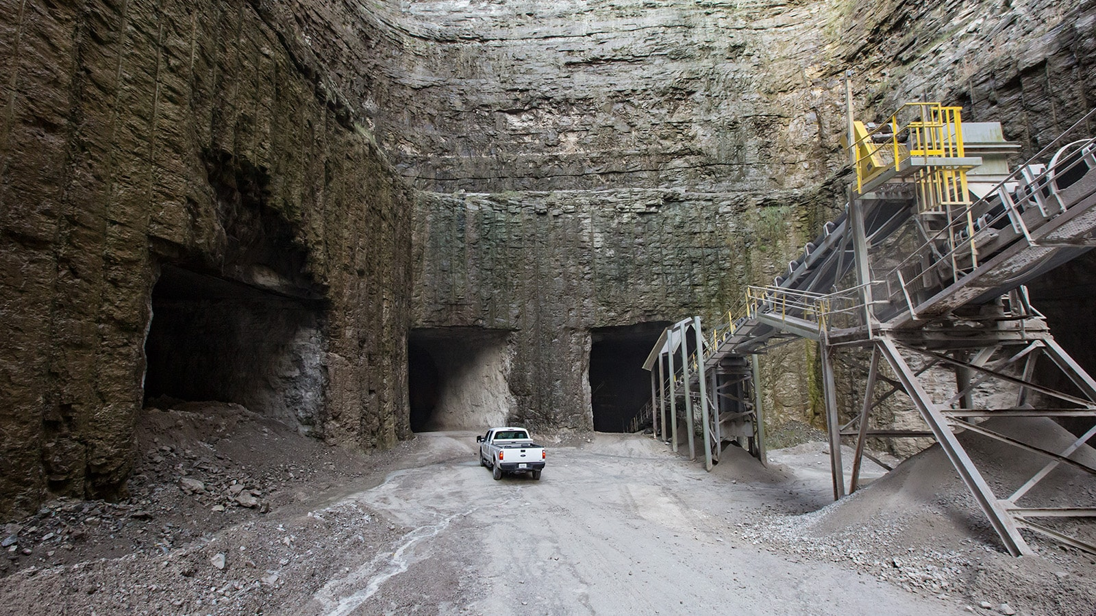 A pickup truck drives into the mine entrance