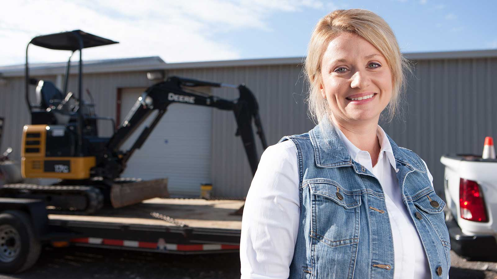 Chasity Crowe-Moore stands in front of a 17G mini excavator on a trailer.