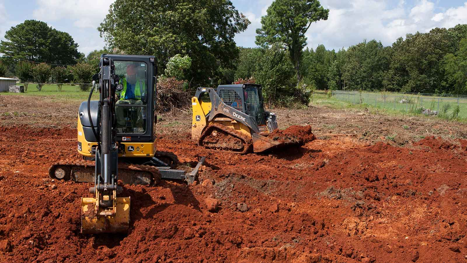 A John Deere compact track loader and mini excavator on a jobsite.