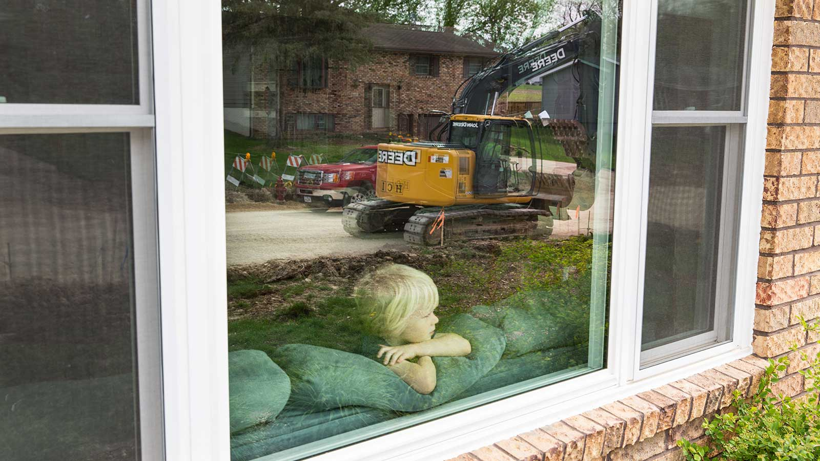 Charlie Koelker watches the work from the window inside his home.