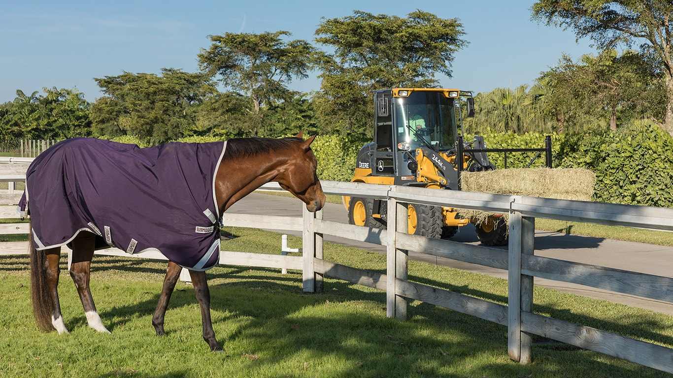 244K-II Wheel Loader hauls a bale past a horse pen