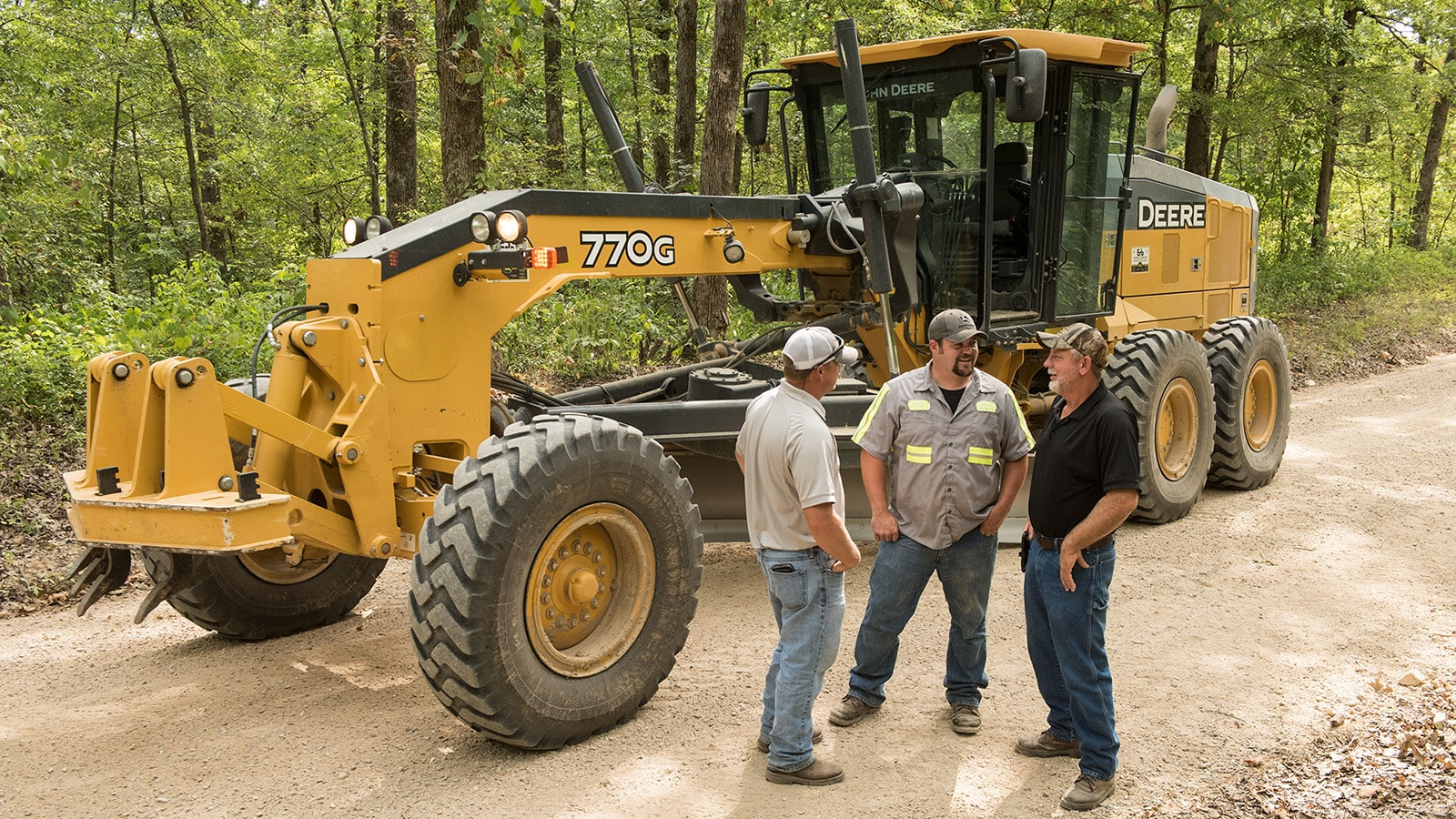 Three men stand in front of a 770G motor grader talking on a wooded gravel road