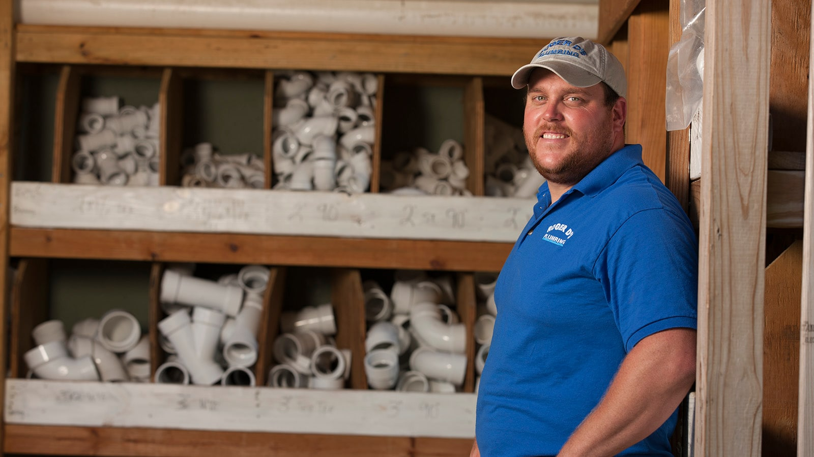 Roger Haislep stands in front of his PVC plumbing parts bins.