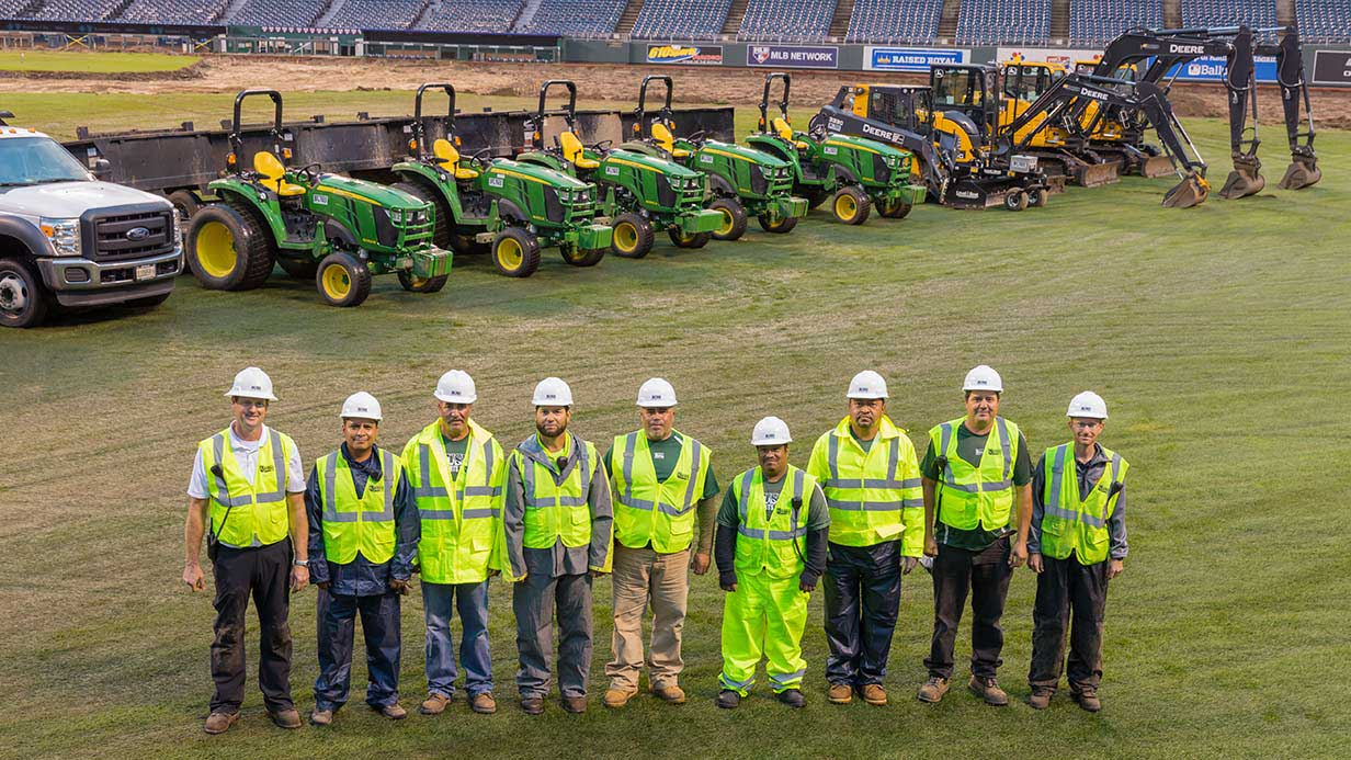 General contractor Steve Bush stands with his team in front of their all-Deere equipment fleet.