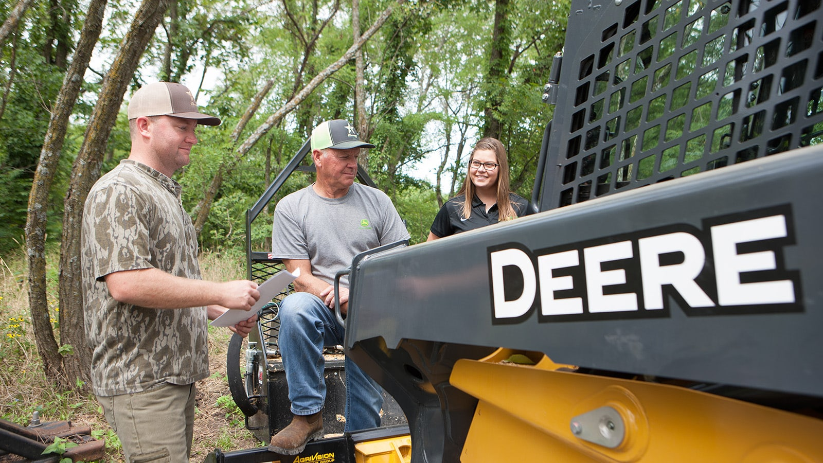 David Lindsey and Jeff Lindsey stand by their 333G compact track loader with a representative from their John Deere dealership.