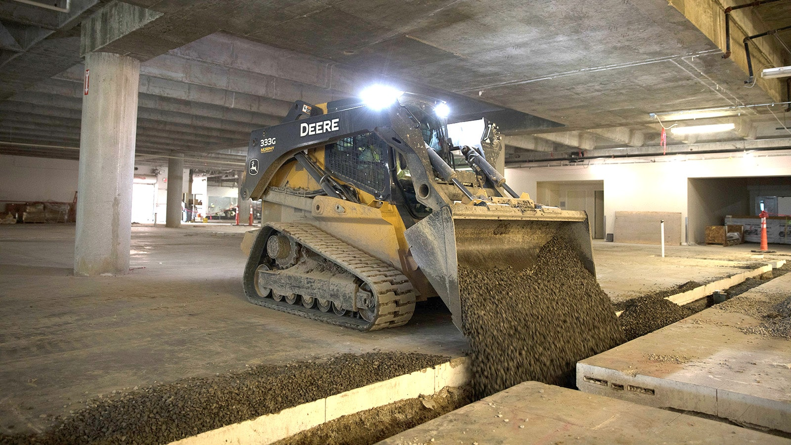 333G Compact Track Loader dumps a load of dirt into a gap in a parking garage site