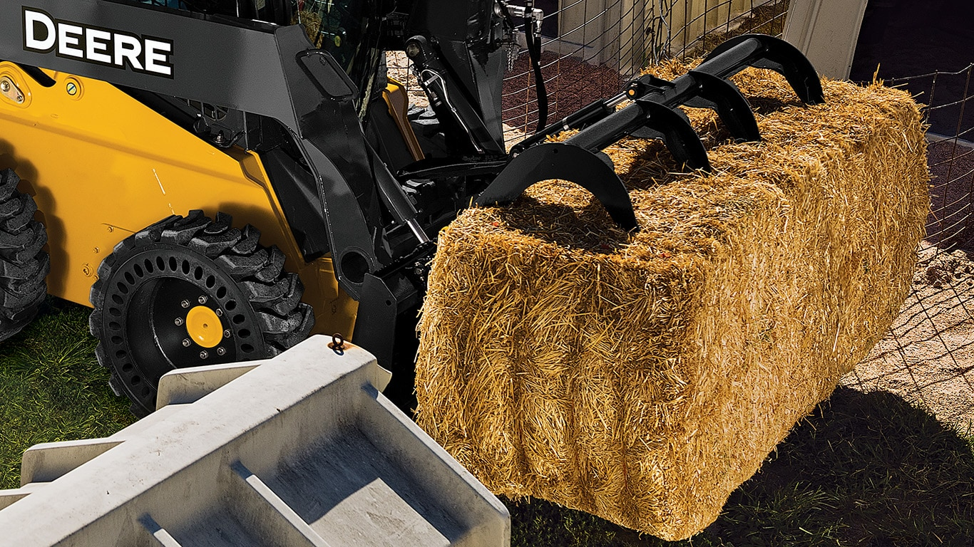 318E Skid Steer with grapples hauling a bale of straw.