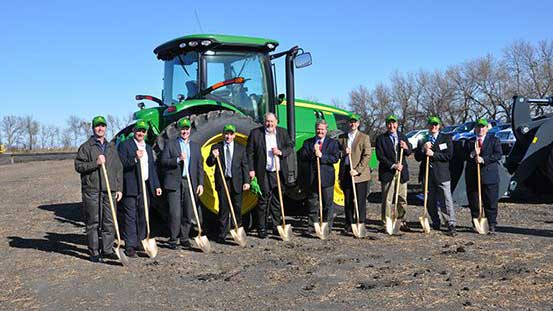 A group of men with shovels in front of a John Deere tractor