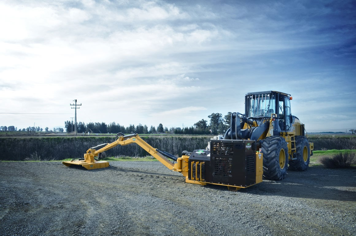 John Deere Wheel Loader with a Diamond Boom Mower Attachment in a Field on Gravel