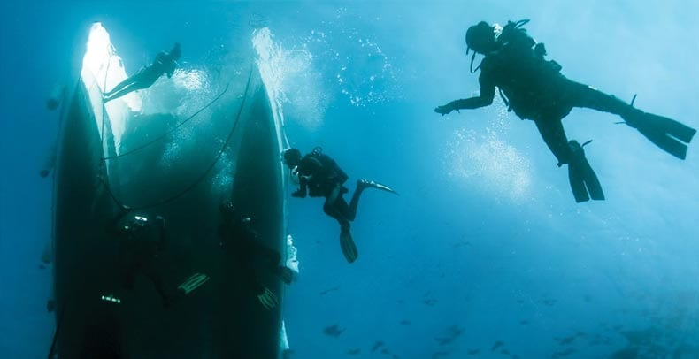 Divers under water with a ship and fish