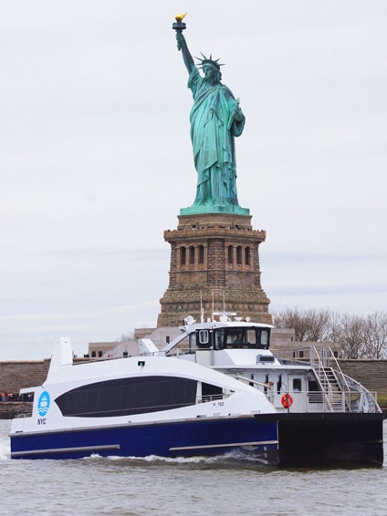 NYC ferry in front of the Statue of Liberty