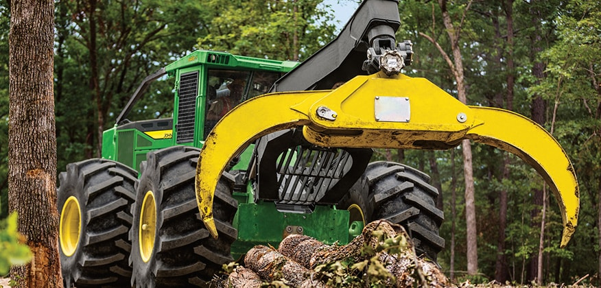 648L-II Skidder opens its grapple wide to pick up a load of logs