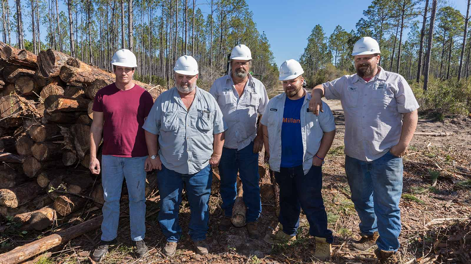 Steven McMillan stands with his logging crew next to a pile of trees in Tate's Hell State Forest