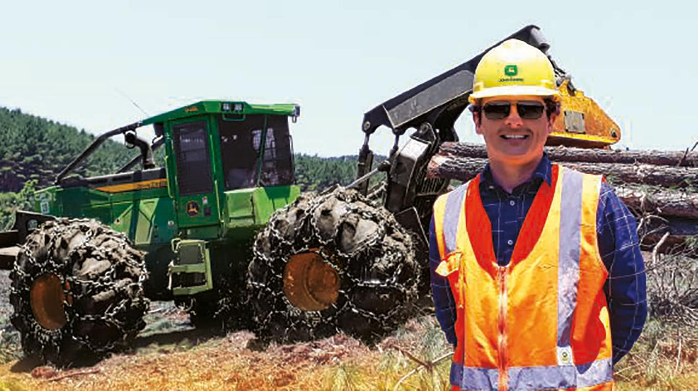 Crystian Fracasso stands in front of a forestry skidder on a sunny day