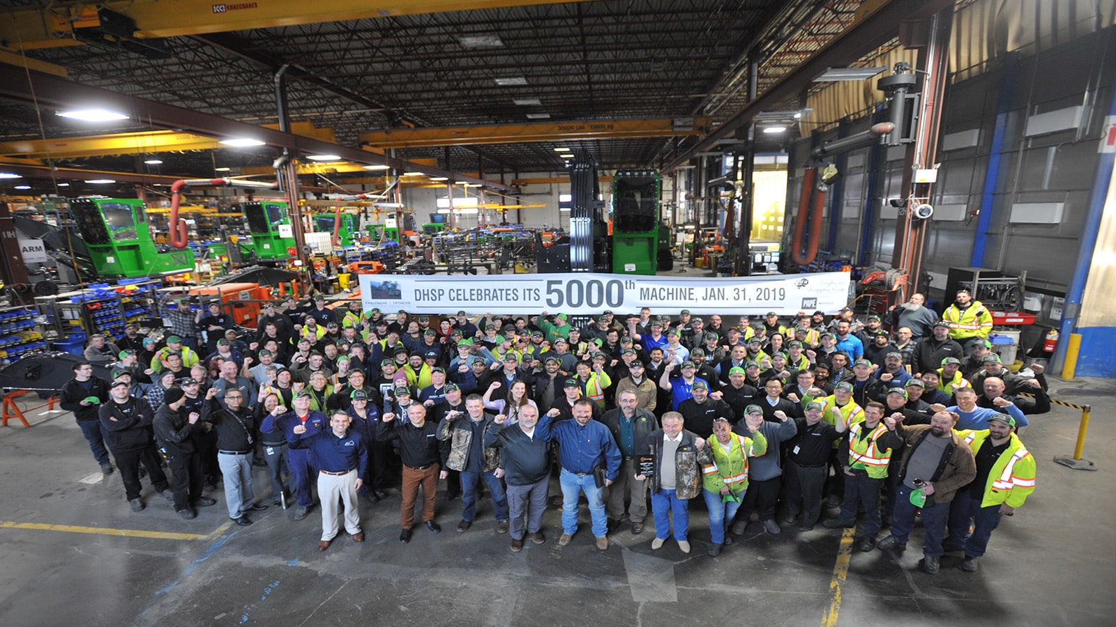 Factory workers gather around the 5000th forestry swing machine produced in Langley, British Columbia.