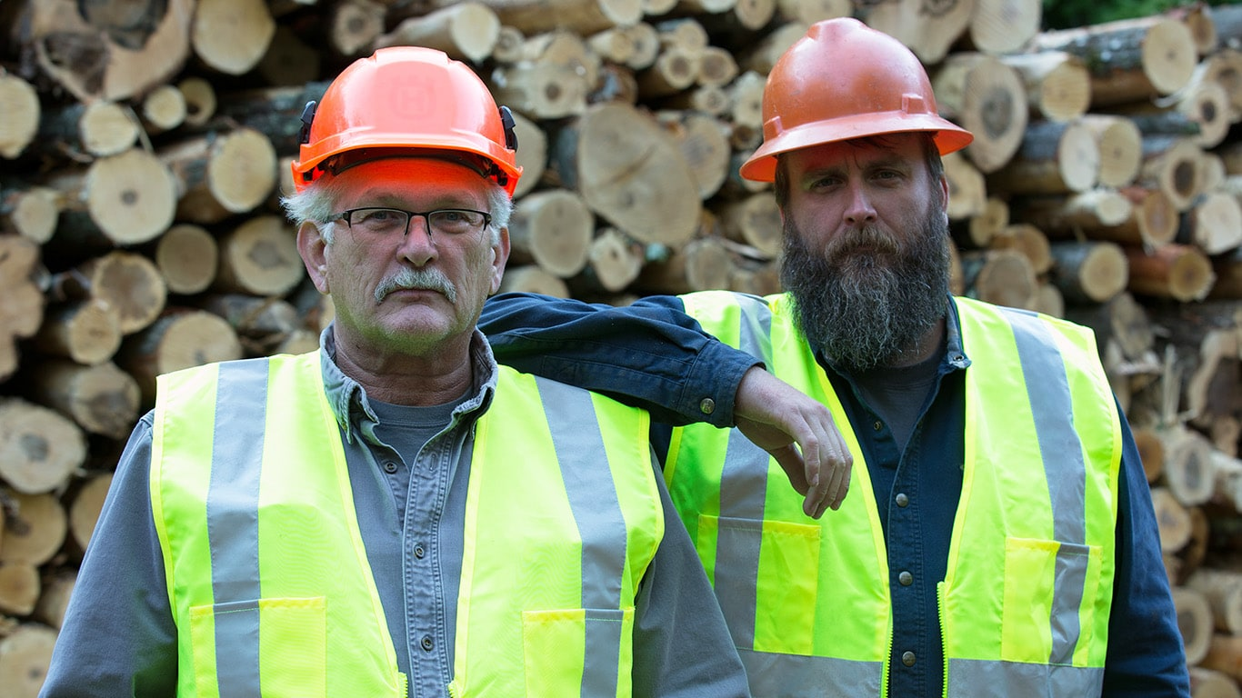 Dameon Harris and Tom Reynolds, co-owners of R&H Logging, stand in front of a pile of logs.