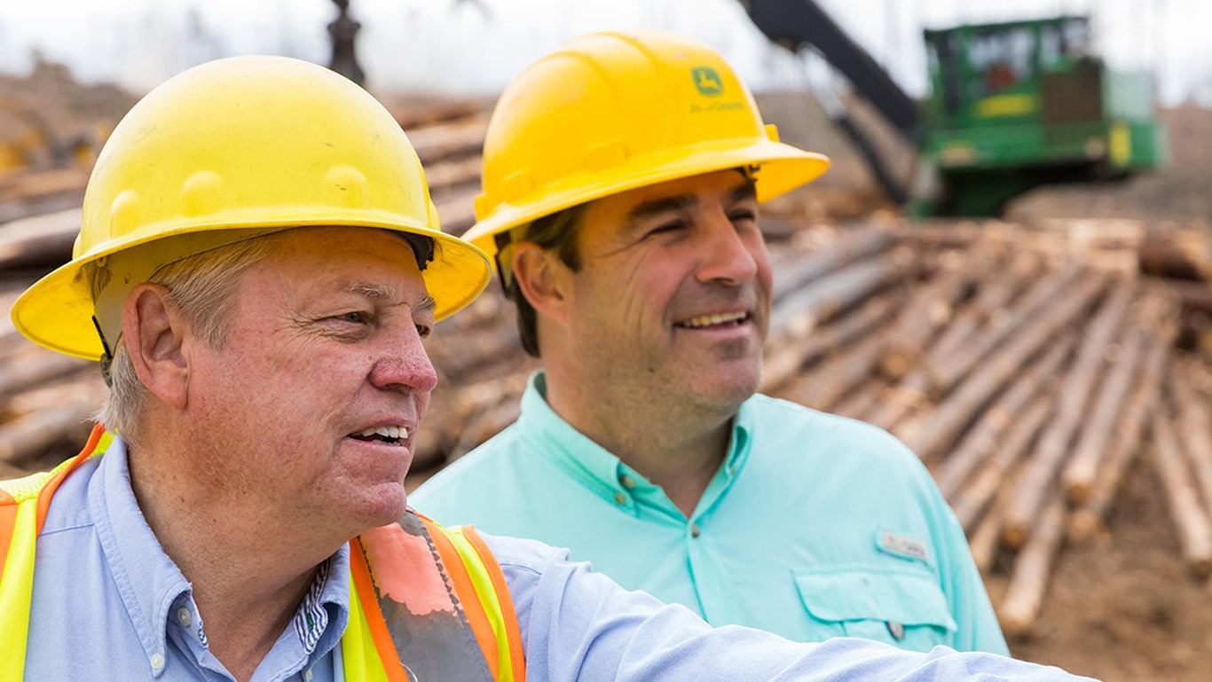 Two men on a logging jobsite smile, talking to each other, in front of a log pile and swing machine