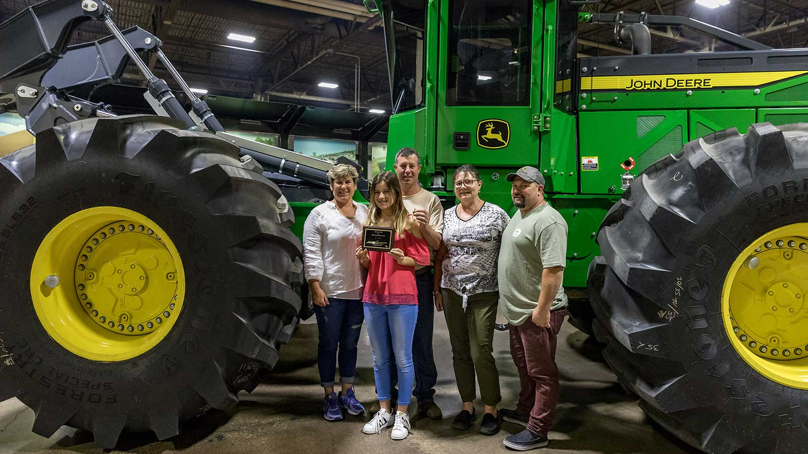 Ferguson and his family line up for pictures next to their new 848L Skidder as it comes off the factory line.