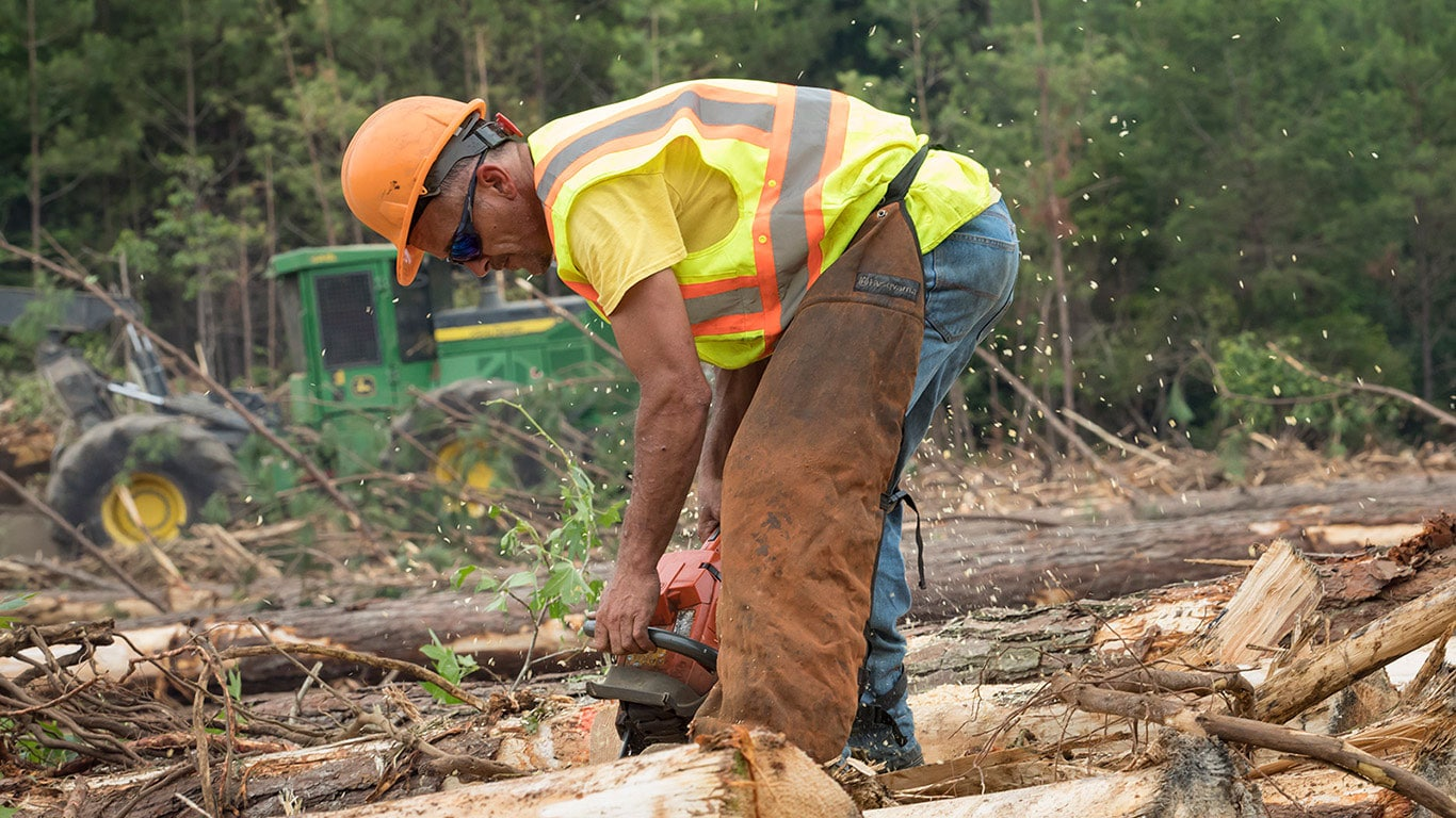 A logger in hard hat, safety glasses and vest operates a chain saw while a John Deere machine works in the background