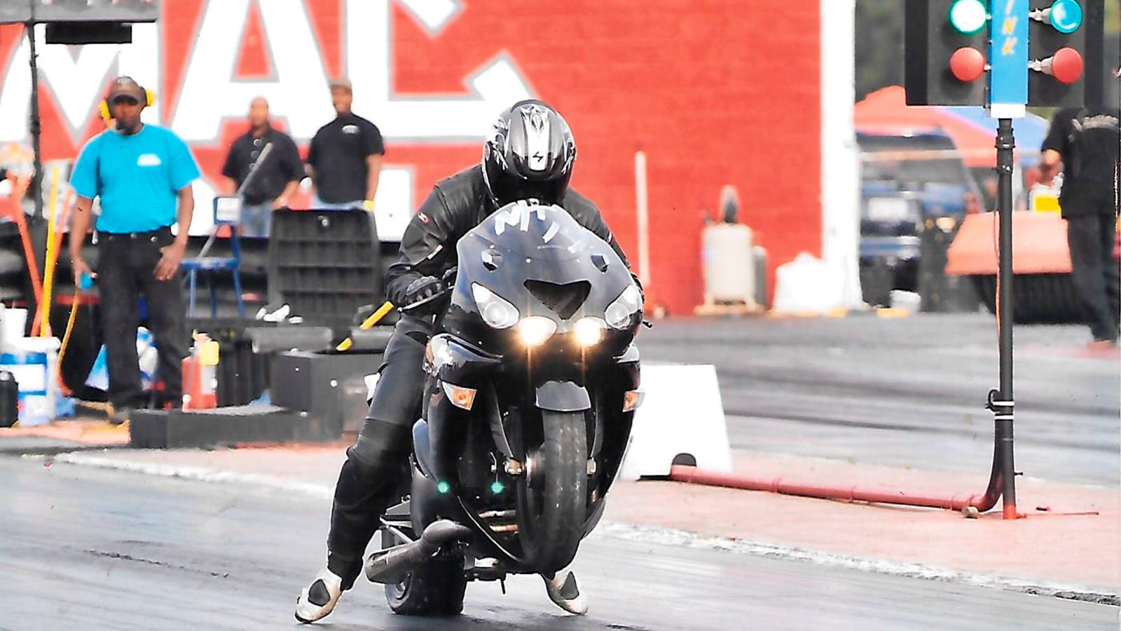 Wayne Sugg takes off from the starting line on his motorcycle in a drag race.