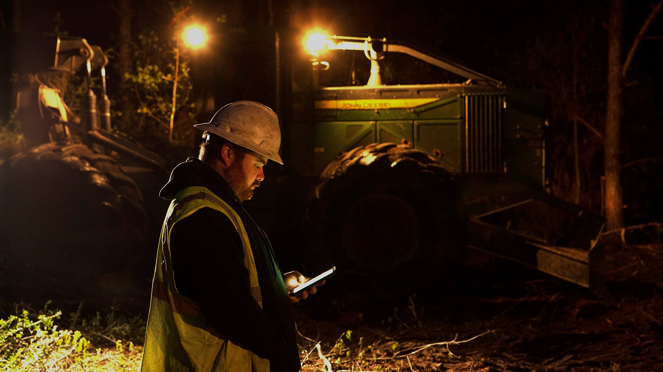 The light from a phone glows in the hands of Thomas Johnson as his skidder lights up the background of a dark logging jobsite.