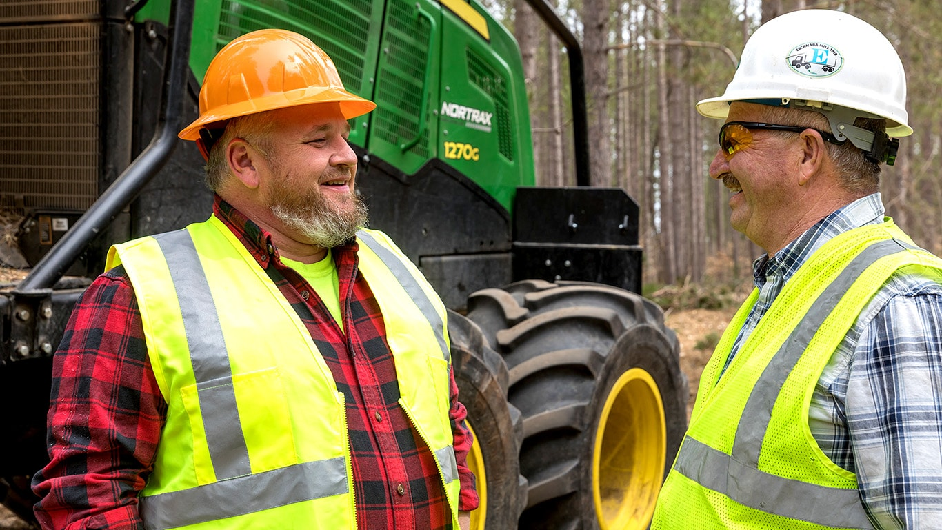 Paul Burton and Tuffy Burton smile as they talk to each other in front of a 1270G Wheeled Harvester