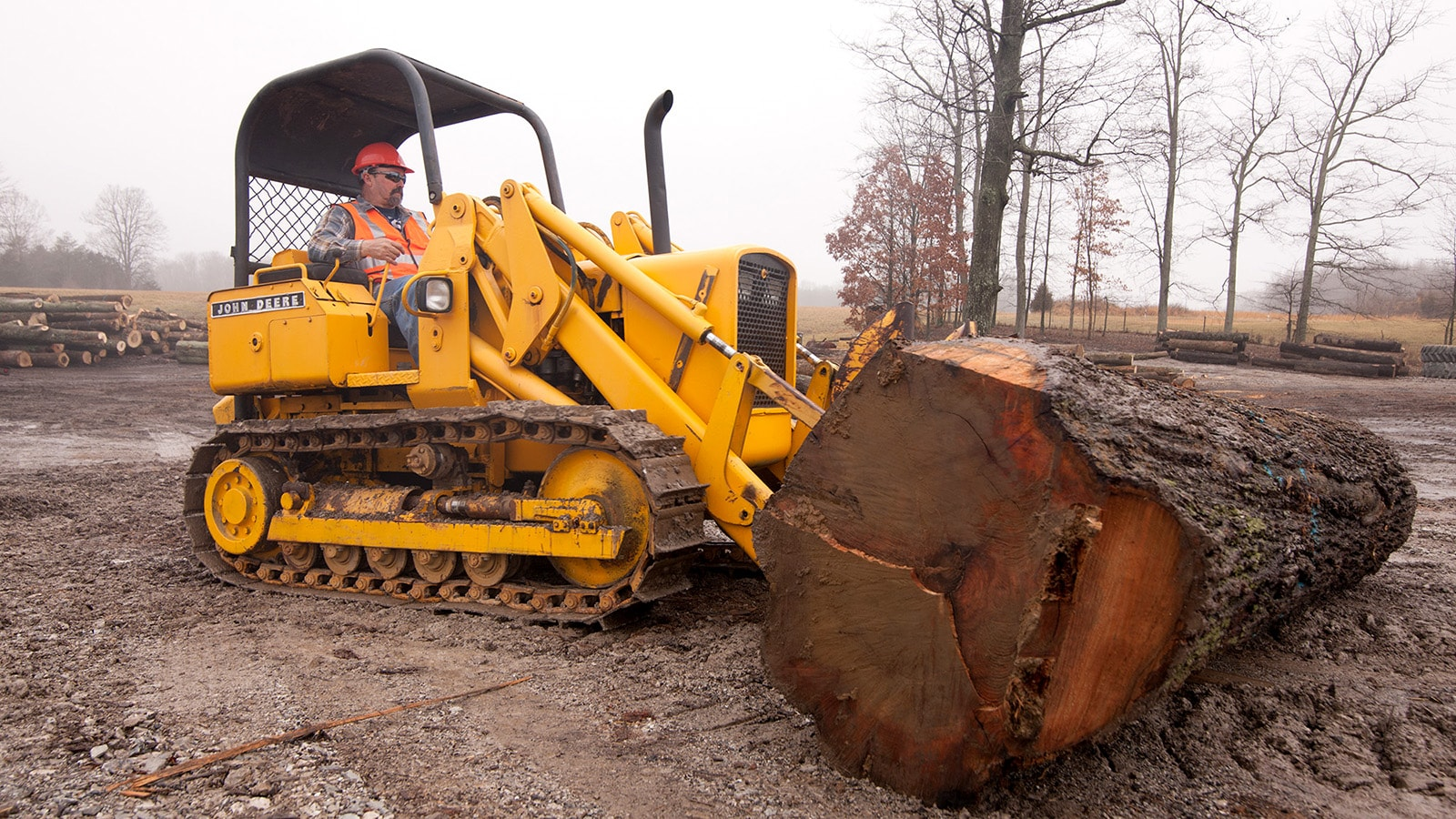 Danny Richards uses a John Deere crawler to move a large log